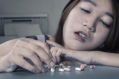 使用麻醉形状的药片的女孩 库存图片