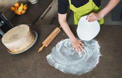 使用滚针的妇女白色方旦糖为装饰的蛋糕,手细节做准备 免版税库存图片