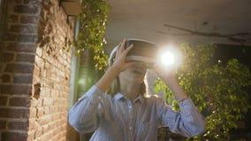 使用3D虚拟现实耳机的美丽的少妇 虚拟现实比赛 学生女孩高兴地使用头 影视素材