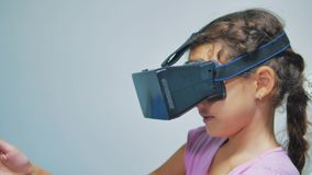 使用3d风镜的愉快的年轻女孩一个虚拟现实耳机 有VR设备的惊奇的妇女 女孩愉快微笑 股票录像