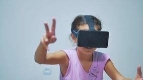 使用3d风镜的愉快的年轻女孩一个虚拟现实耳机 有VR设备的惊奇的妇女 女孩愉快微笑 股票视频