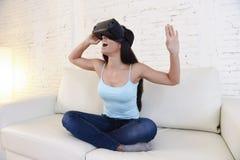 使用3d风镜被激发的愉快的妇女在家客厅沙发长沙发观看360虚拟现实 免版税库存图片