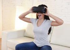 使用3d风镜被激发的愉快的妇女在家客厅沙发长沙发观看360虚拟现实 免版税图库摄影