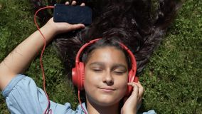 使用a,有长的黑发的可爱的女孩在草说谎在公园并且听到在红色耳机的音乐 影视素材