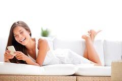 使用app微笑的智能手机妇女愉快在沙发 免版税图库摄影