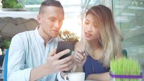 使用app的多文化夫妇在一起智能手机 免版税库存照片