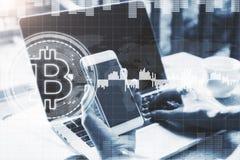 使用bitcoin膝上型计算机和智能手机的手 免版税库存照片