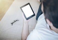 使用e书读者或片剂计算机,供以人员放松在长沙发 免版税库存照片