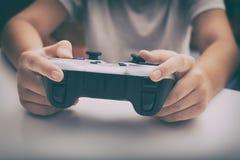 使用gamepad,年轻男孩打电子游戏 免版税库存照片