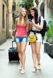 使用GPS导航员的两个女孩为发现一个方式 免版税库存照片
