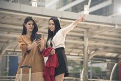 使用gps的少妇游人在一个巧妙的电话映射在城市 免版税图库摄影