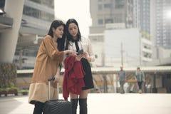 使用gps的少妇游人在一个巧妙的电话映射在城市 图库摄影