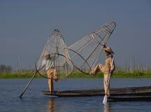 使用Inle湖传统方法的两位渔夫  免版税库存图片
