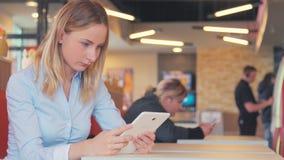 使用ipad片剂触摸屏的美丽的少妇在咖啡馆 股票视频