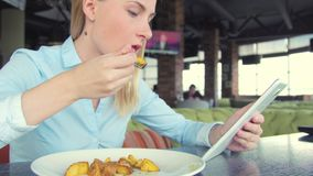 使用ipad片剂计算机触摸屏幕的美丽的妇女在咖啡馆 股票录像