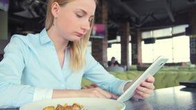 使用ipad片剂计算机触摸屏幕的美丽的妇女在咖啡馆 影视素材