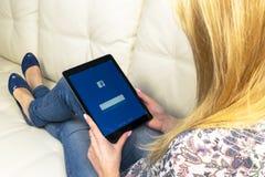 使用iPad的妇女手赞成与在屏幕上的Facebook主页 Facebook最大的社会网络网站 facebook.com主页 com 免版税图库摄影