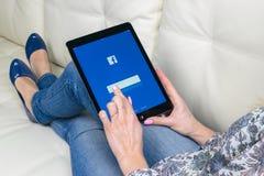 使用iPad的妇女手赞成与在显示器屏幕上的Facebook主页 Facebook最大的社会网络网站 主页 免版税库存照片