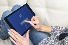 使用iPad的妇女手赞成与在显示器屏幕上的Facebook主页 Facebook最大的社会网络网站 主页 库存照片