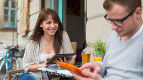 使用ipad的微笑的妇女,在使用智能手机的前景人 库存图片