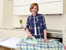 使用iro的愉快的妇女或主妇电烙的衬衣在家厨房 库存照片