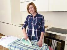 使用iro的愉快的妇女或主妇电烙的衬衣在家厨房 图库摄影
