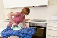 使用iro的愉快的妇女或主妇电烙的衬衣在家厨房 免版税库存照片