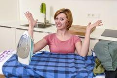 使用iro的愉快的妇女或主妇电烙的衬衣在家厨房 库存图片