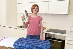 使用iro的愉快的妇女或主妇电烙的衬衣在家厨房 免版税库存图片