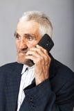 使用MOBIL电话的一个年长人的画象 库存图片
