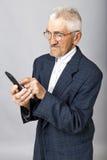 使用MOBIL电话的一个年长人的画象 免版税库存照片