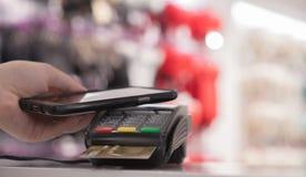 使用NFC技术的妇女为付款在商店 库存图片