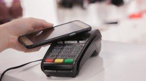 使用NFC技术的妇女为付款在商店 免版税库存图片