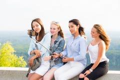 使用selfie棍子,快乐的小组年轻微笑的妇女做一selfie 免版税库存图片