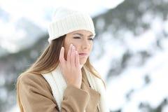 使用sking的保护奶油的恼怒的妇女在冬天 免版税库存照片