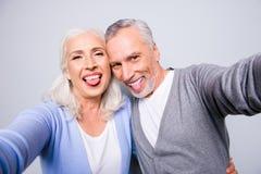 使用smartph,疯狂的质朴的滑稽的年长夫妇采取selfie 免版税图库摄影