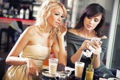使用smartphone的二名妇女 免版税库存照片
