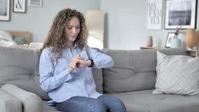 使用smartwatch的卷发妇女,当坐沙发时