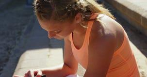 使用smartwatch的女运动员在运动会比赛地点4k 影视素材