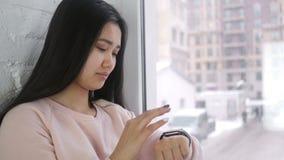 使用smartwatch的年轻亚裔妇女为浏览,坐在窗口 影视素材