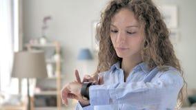 使用smartwatch的年轻卷发妇女 股票录像