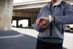 使用smartwatch的母慢跑者在一个晴天 库存图片