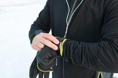使用smartwatch的赛跑者 外面,雪,冬天 库存照片