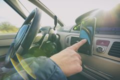 使用smort电话的妇女,当驾驶汽车时 免版税库存照片