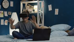 使用VR玻璃和膝上型计算机在床上的男孩 免版税库存图片