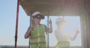 使用VR的两名当代乘员组工作者形象化站立在工地工作,拷贝的未完成的大厦的项目 影视素材