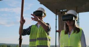 使用VR的两名当代乘员组工作者形象化站立在工地工作,拷贝的未完成的大厦的项目 股票视频