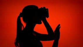 使用VR的少妇黑剪影360块玻璃 在外形的女性` s面孔在红色背景 股票视频