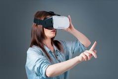 使用VR耳机的情感少妇和体验在灰色背景的虚拟现实 免版税库存照片