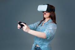 使用VR耳机的情感少妇和体验在灰色背景的虚拟现实 免版税库存图片
